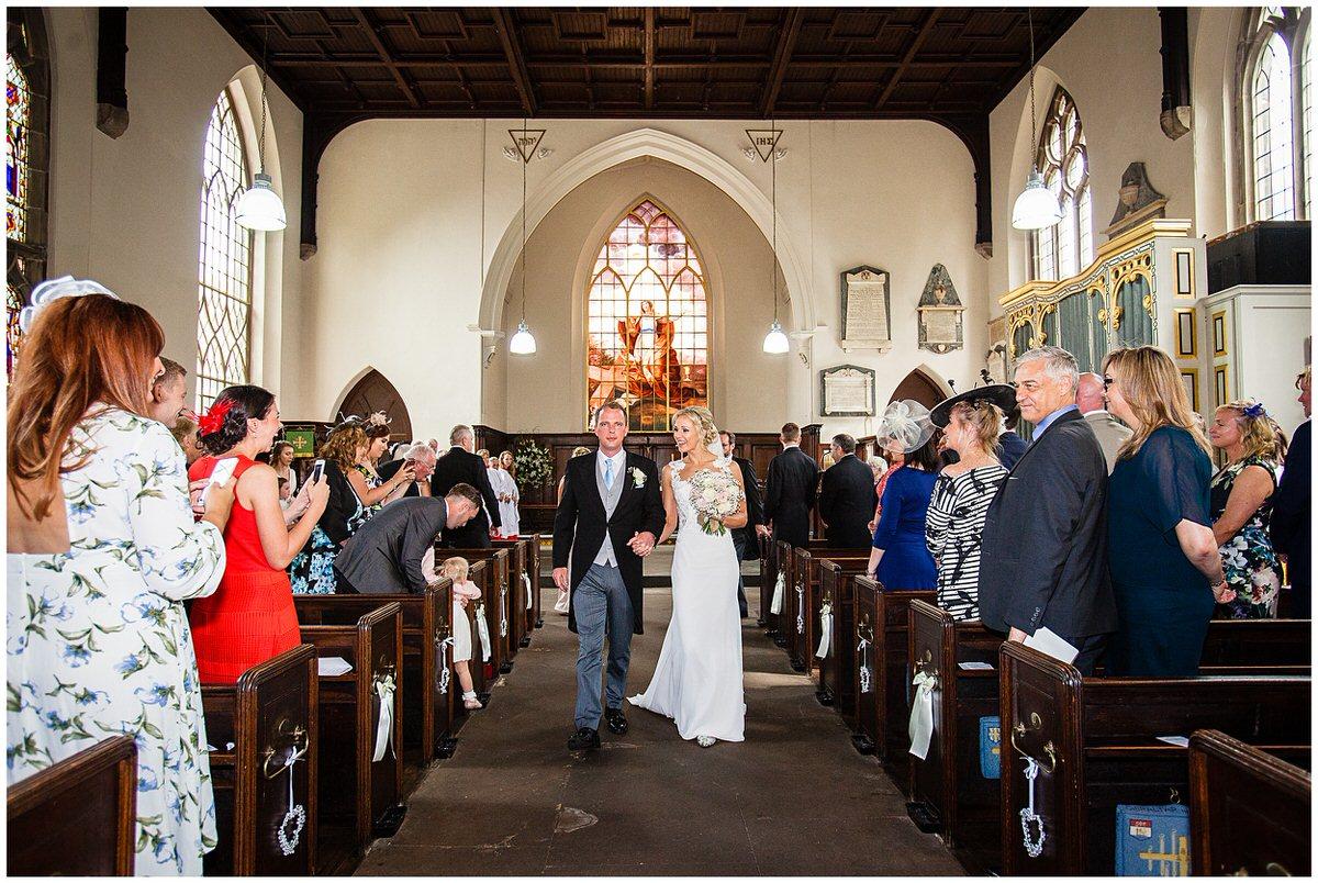 walking down the aisle both looking incredibly hand full length at st alkmunds wedding shrewsbury