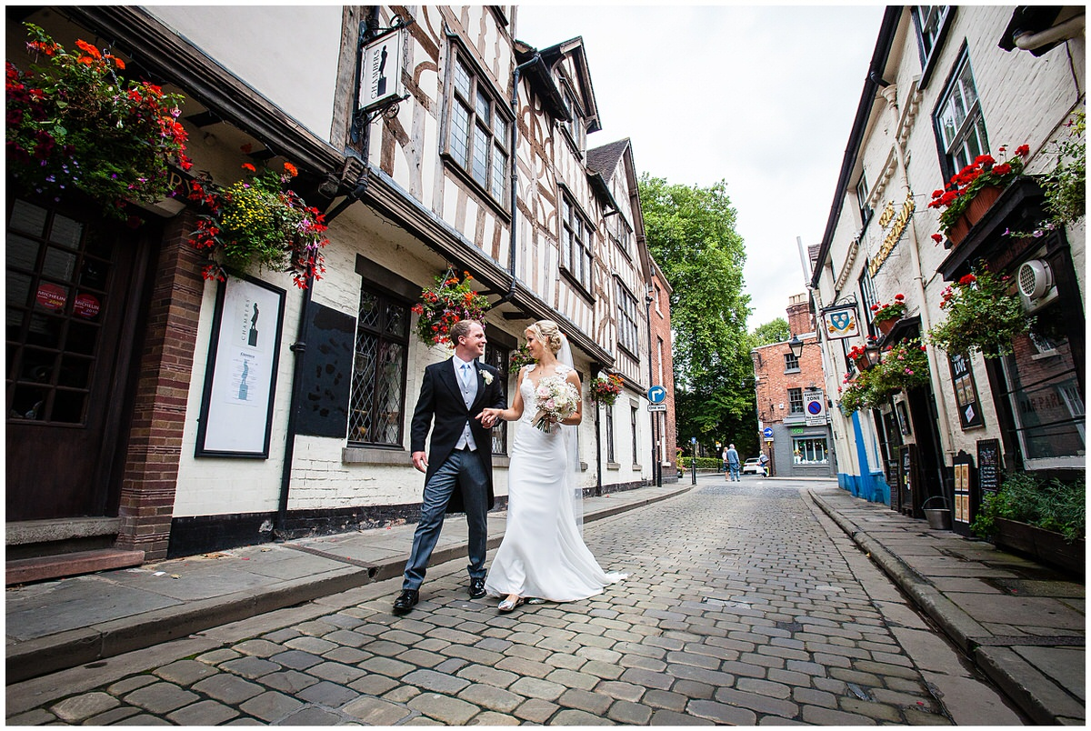 bride and groom walking hand and hand through cobbled streets ofshrewsbury