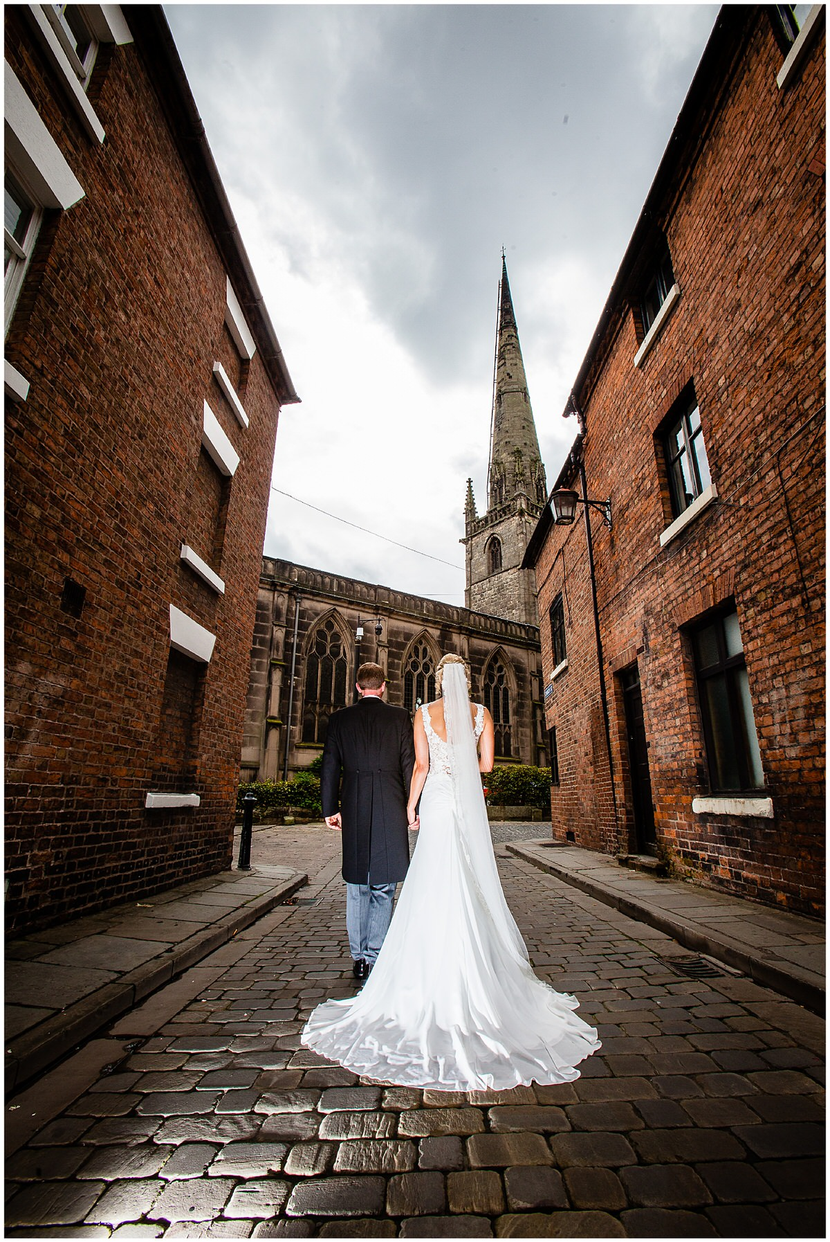 bride and groom walking back to st. alkmunds church