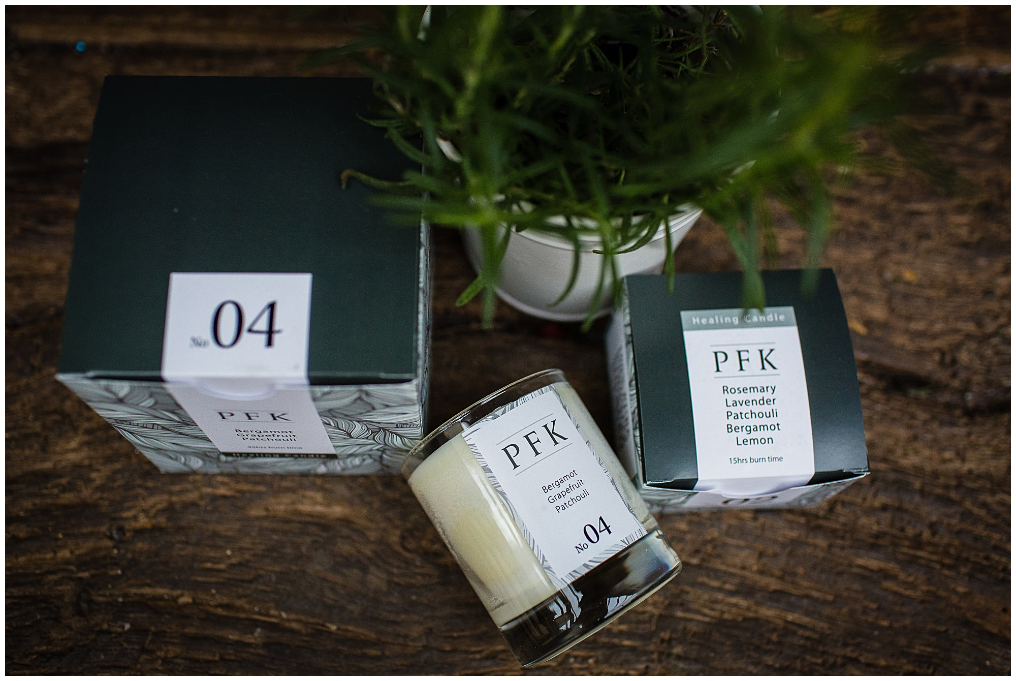 aerial shot of candle lying down amongst green square packaging with rosemary