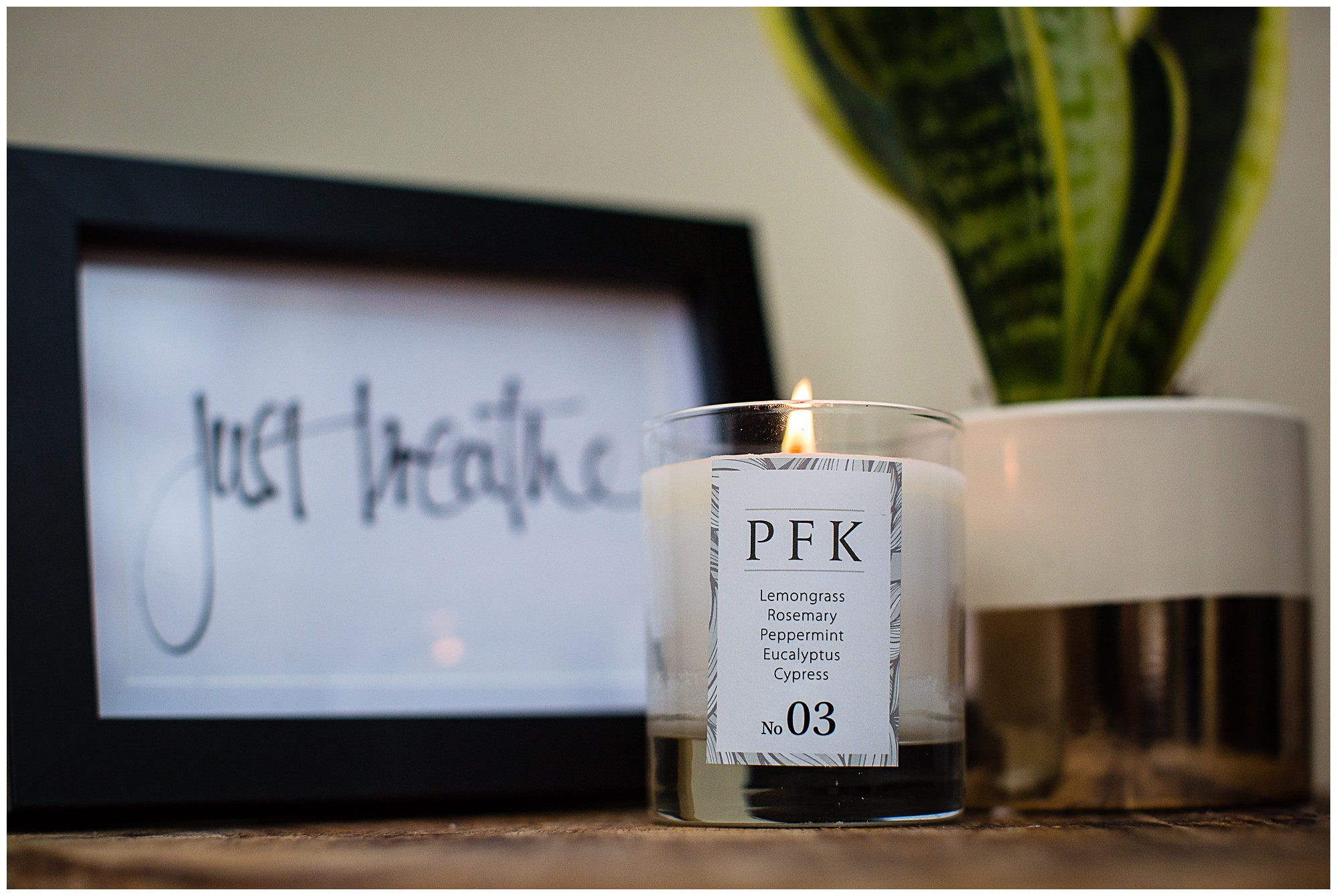 PFK candle lit on a wooden surface with beautiful plant and just breathe in black frame