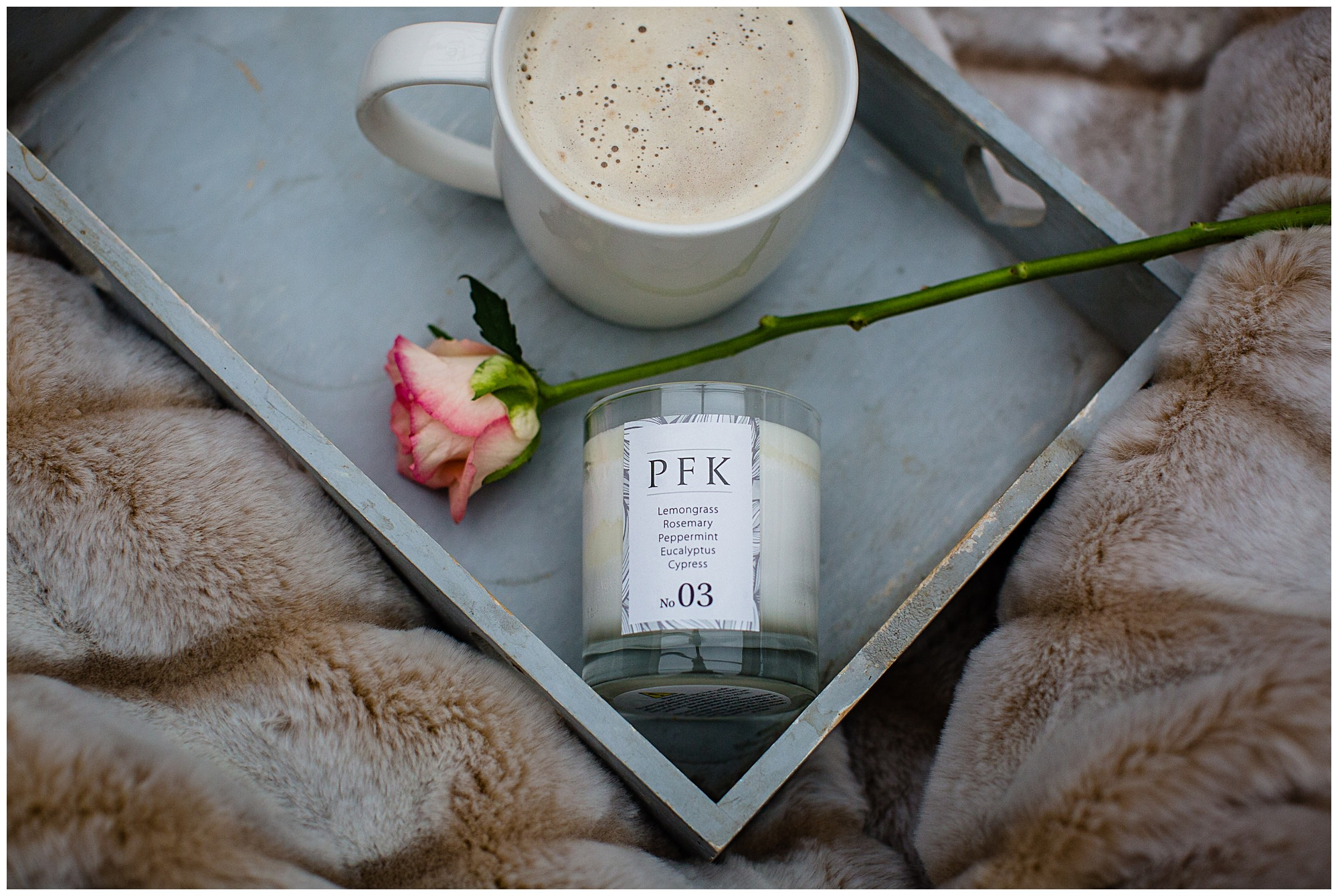 PFK candle on grey tray, with light pink rose and hot cup of coffee amongst fur blanket