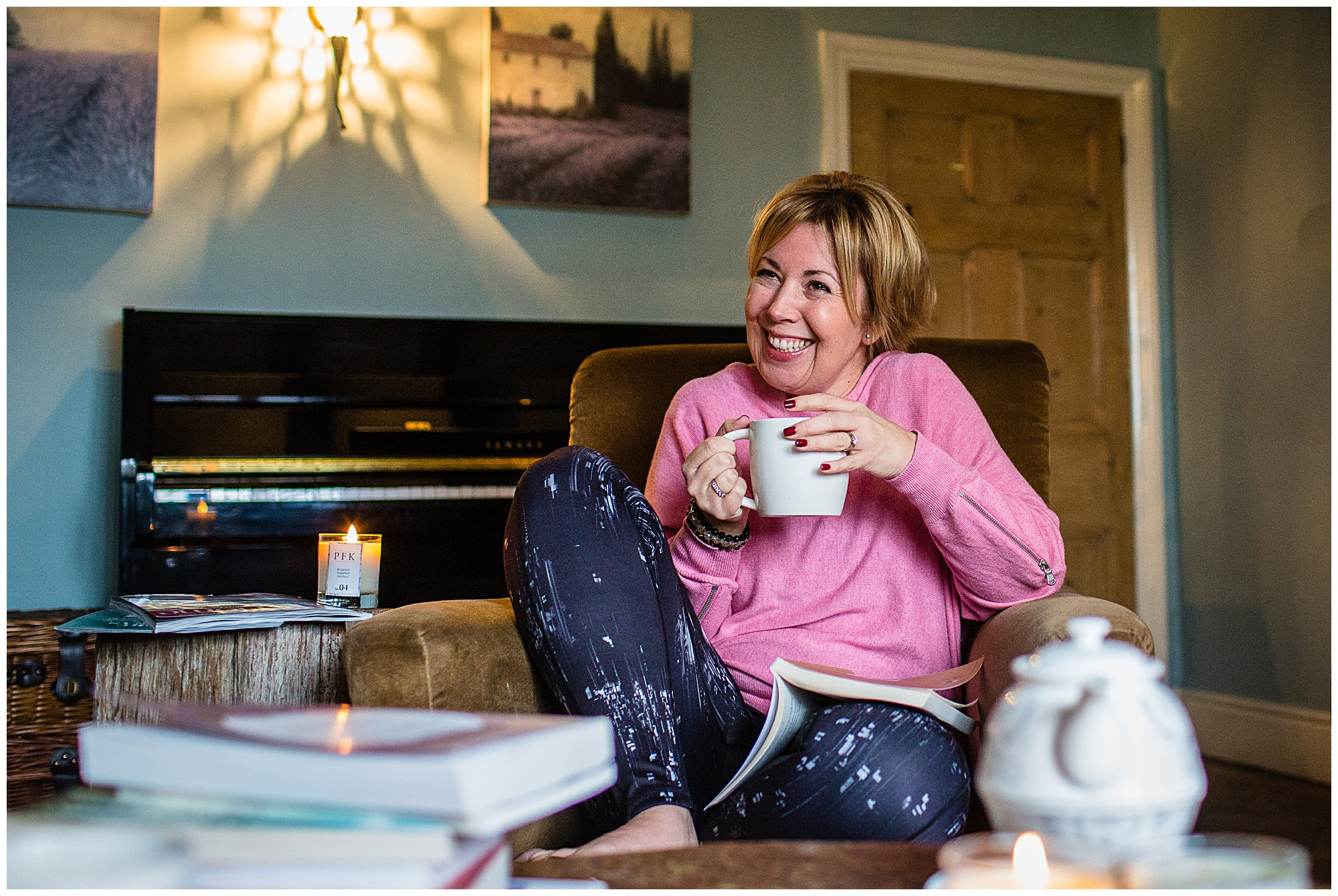 Paula Fox Kirkham candle maker, reading a book and holding a cup of tea laughing, Lifestyle Photographer Shropshire
