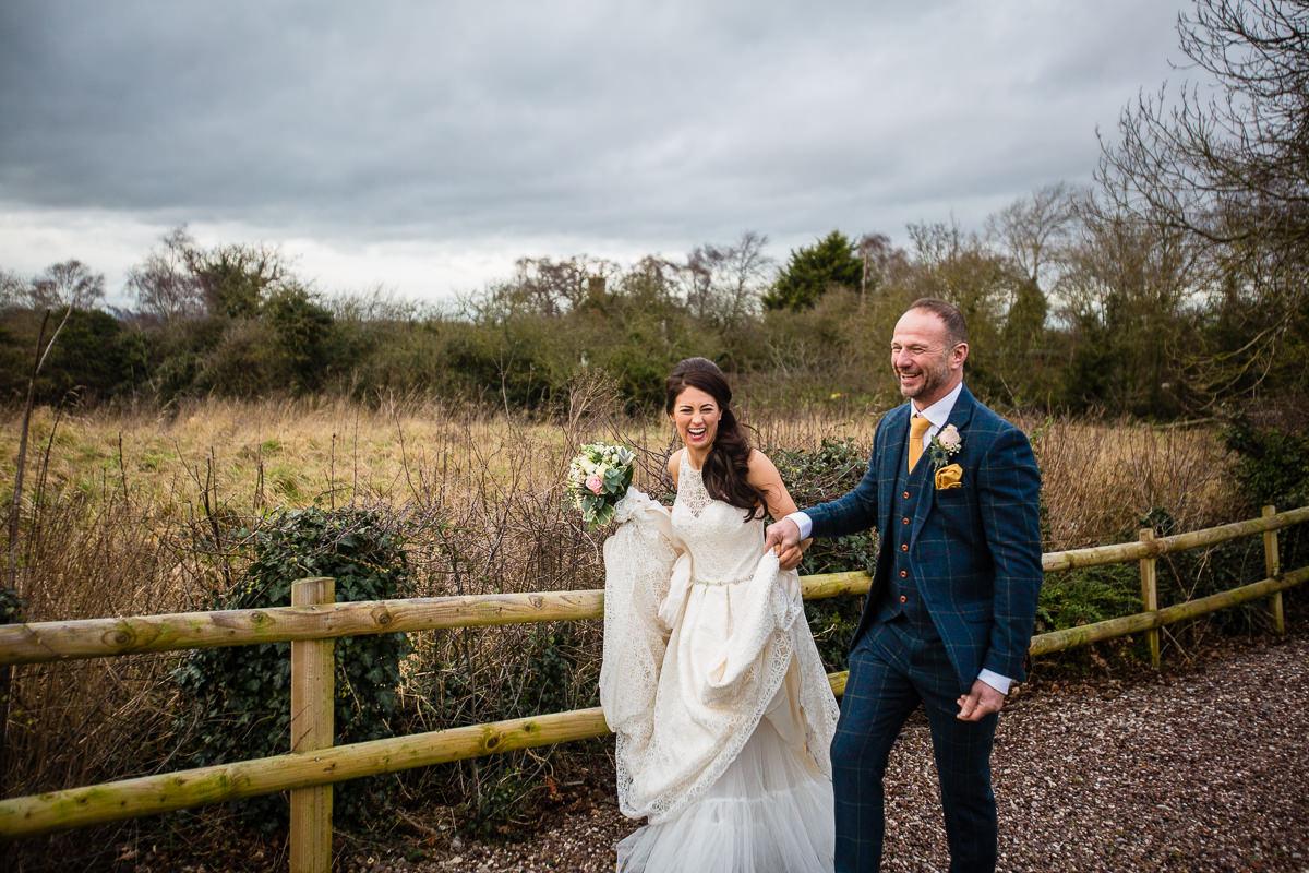 couple walkign through the ground laughing at their cock o barton wedding