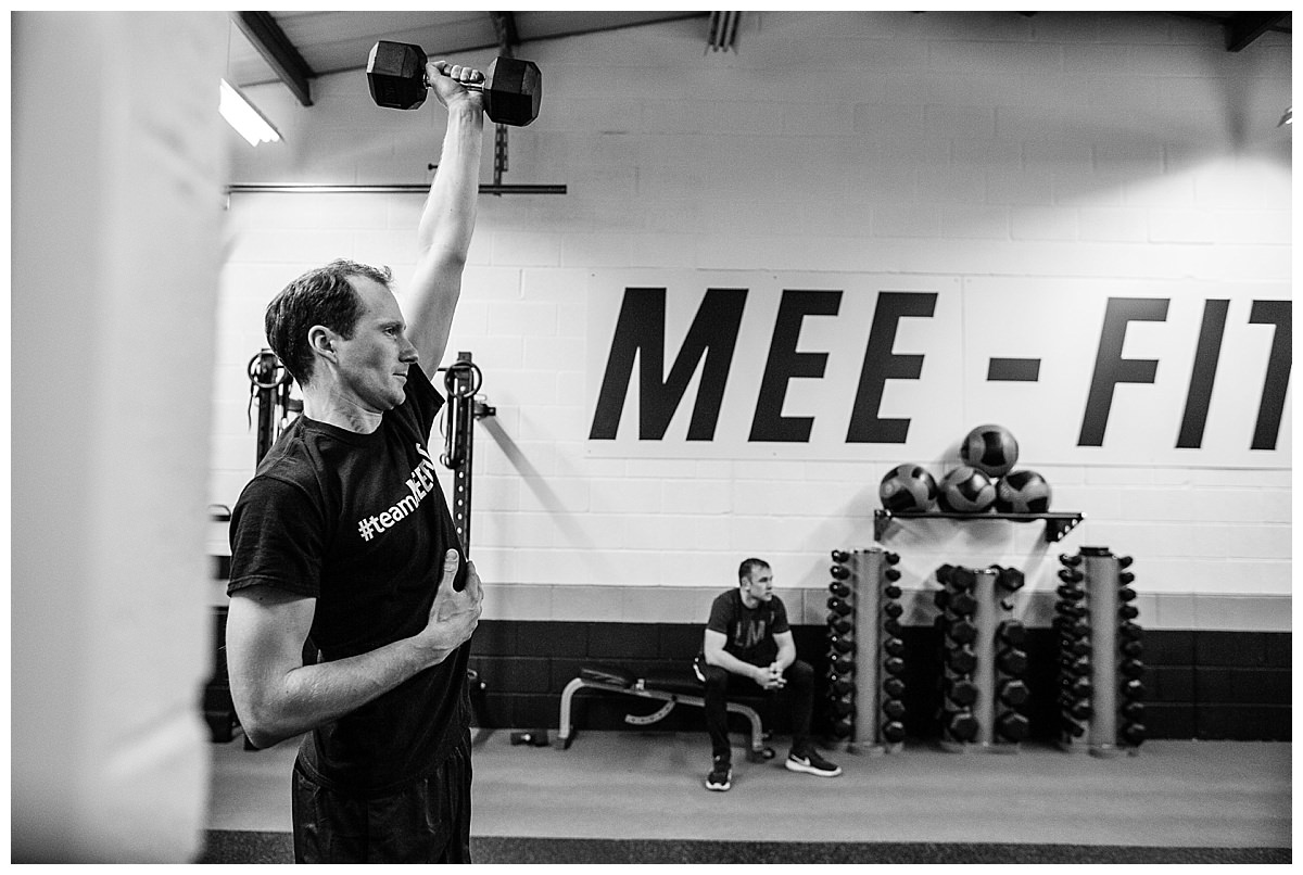 man carrying out a single arm bench press exercise in gym environment - charlotte giddings photography