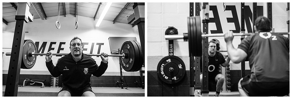 rugby man performing squats at the gym shots of his reflection as he does the exercise