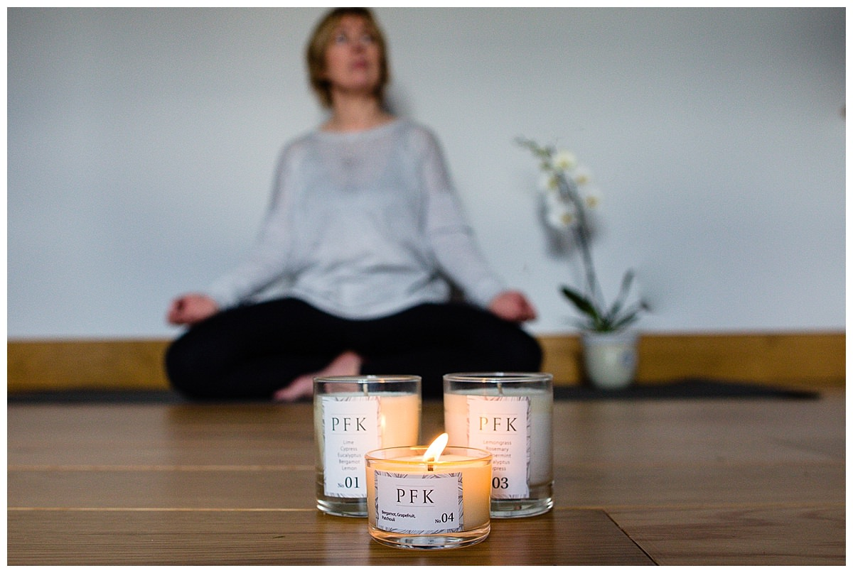 beautiful PFK candles burning in the foreground with Paula performing yoga in the background