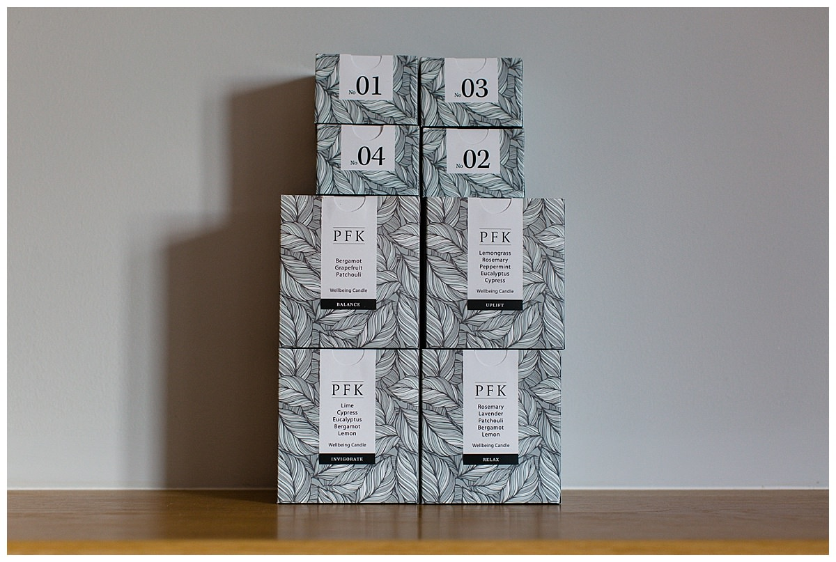 PFK candles in their packaging beautiful stacked up on an oak shelf - charlotte giddings photography