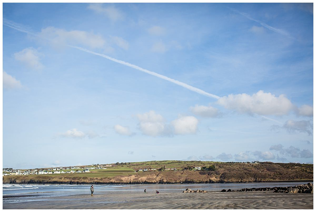 landscape shot of boys playing in the distance at poppit beach, south wales