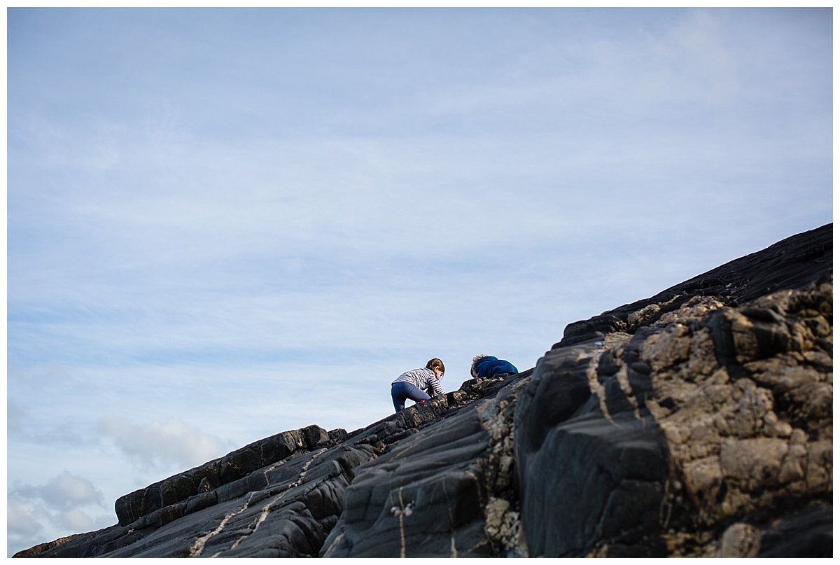 little boy and girl climbing up the rocks on poppit sands beach - charlotte giddings photography