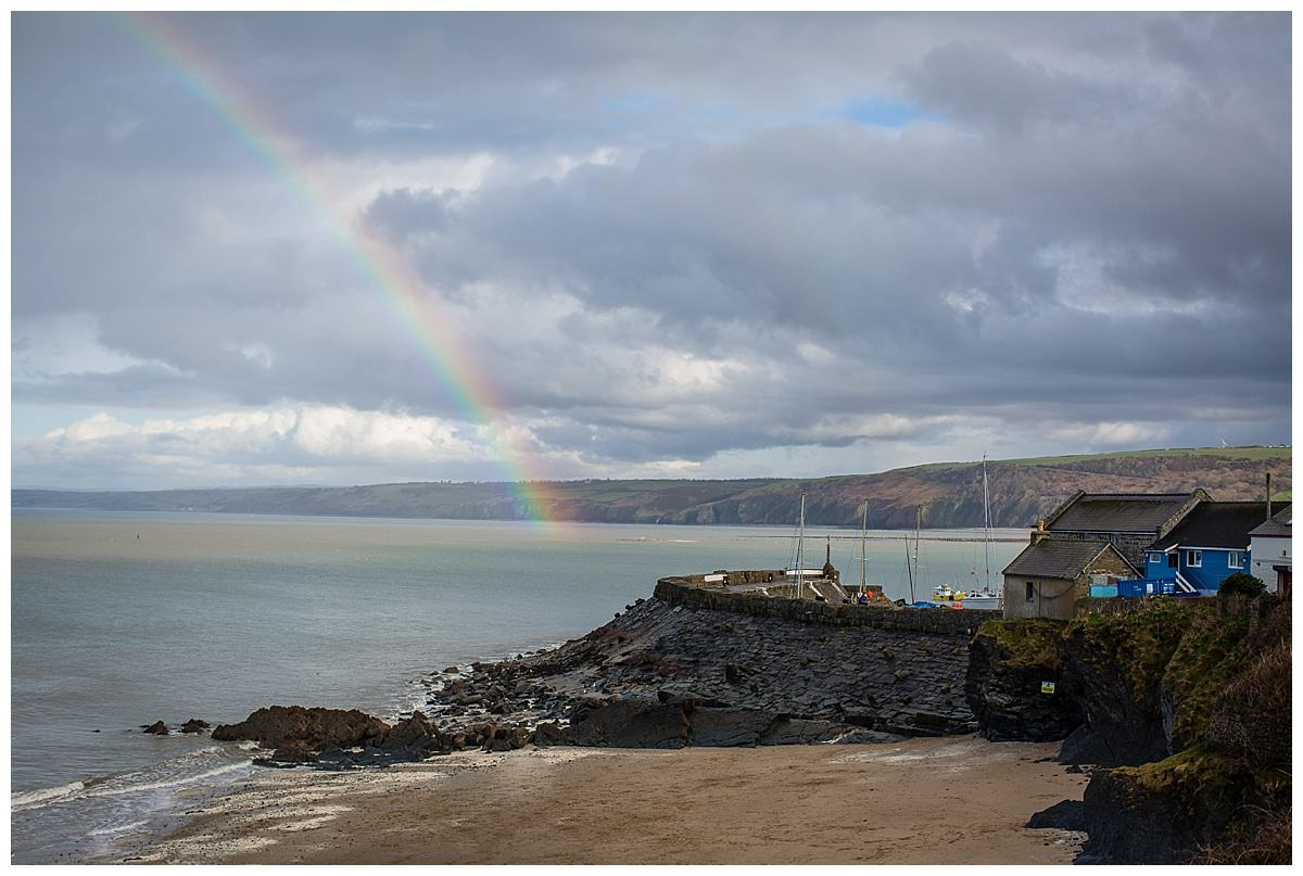 rainbow over new quay beach south wales on a cloudy day in febrauary