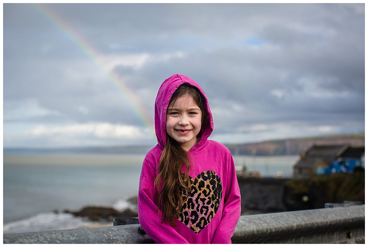 little girl with new quay beach in the background and rainbow on family holiday in south wales