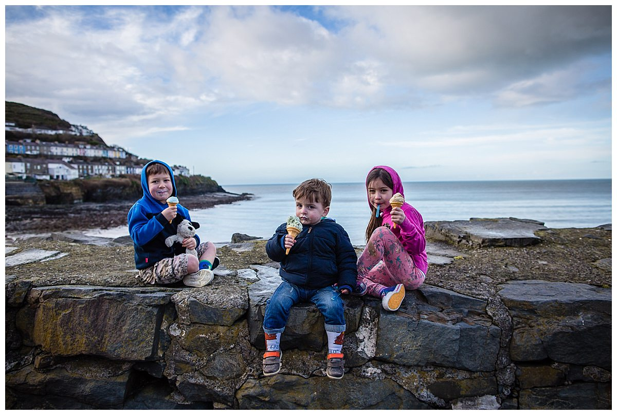 siblings sat on a wall at new quay beach enjoying an ice cream on family holiday in south wales