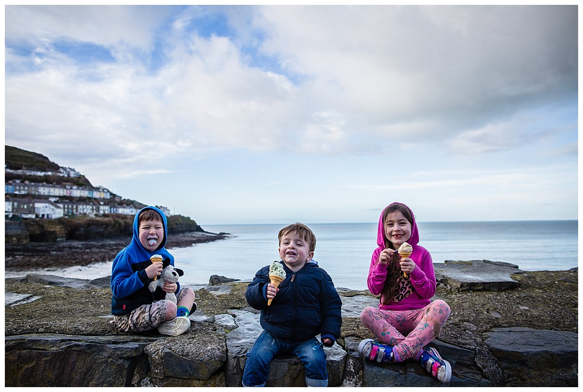 siblings pulling funny faces while eating ice cream on a wall at new quay beach