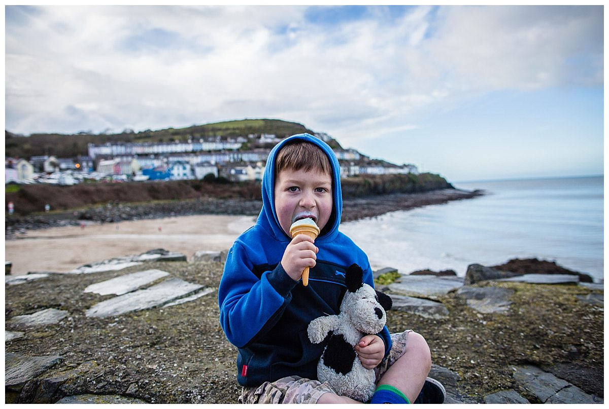 little boy mouth wide open eating ice cream cuddling dog teddy at new quay beach south wales