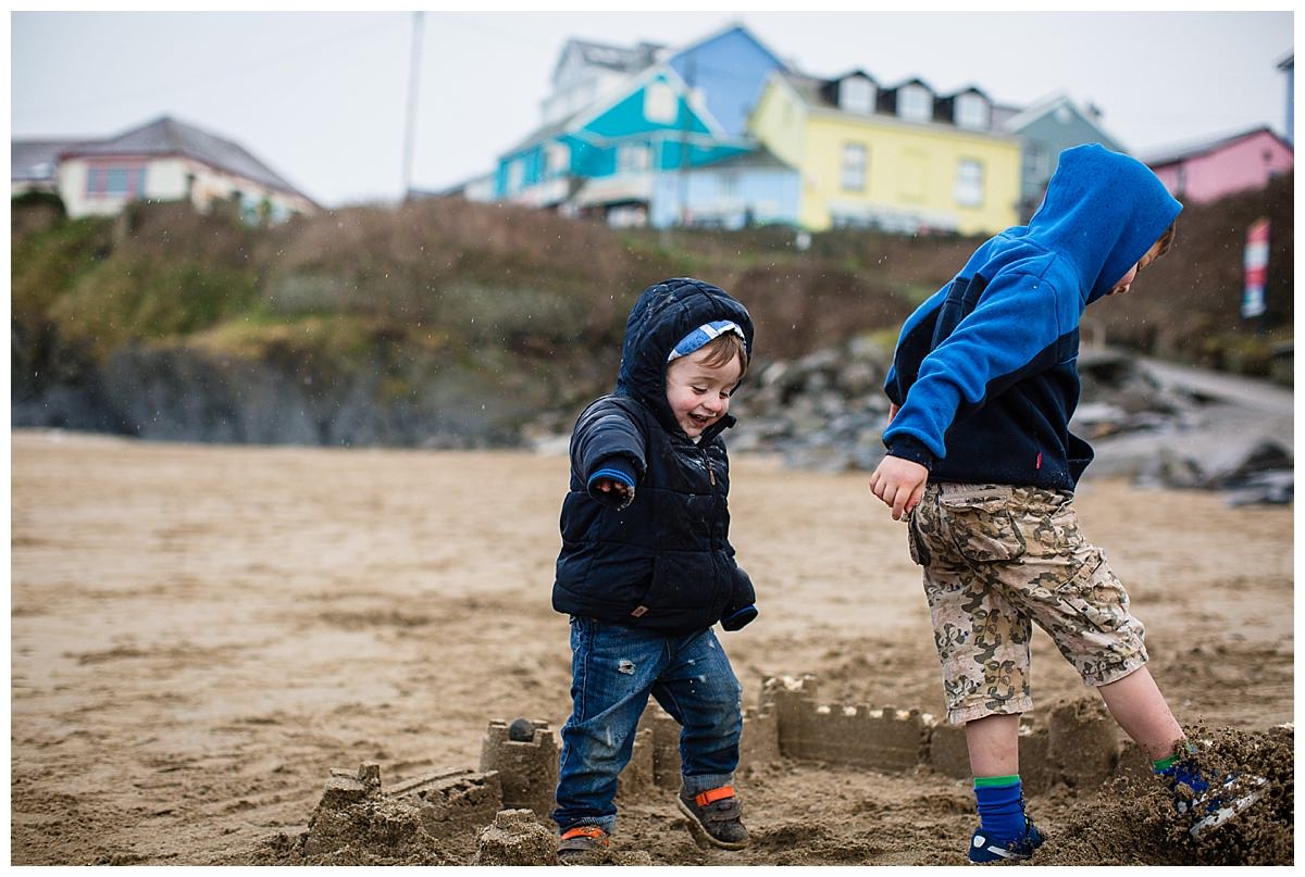 boys laughing and knocking down sand castles on new quay beach - family holiday in south wales