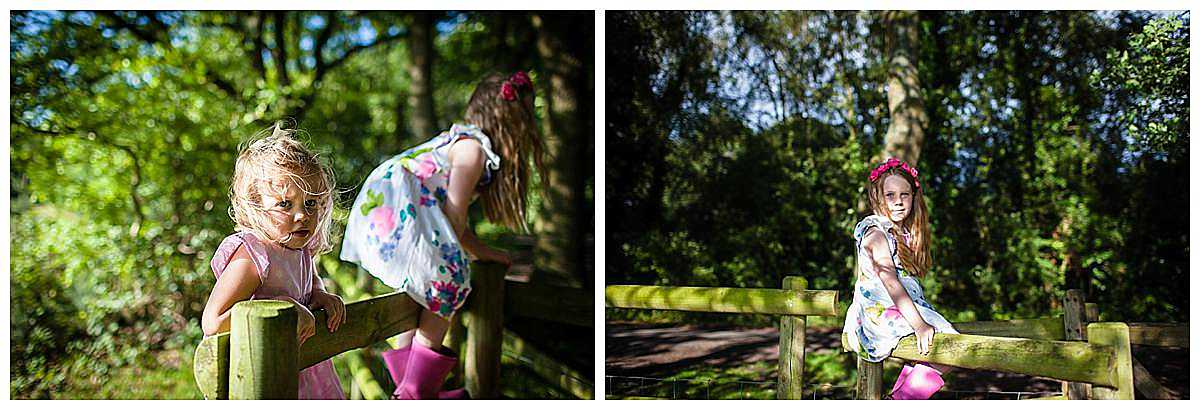 two little girls climbing a wooden gate and looking moody at the camera - shropshire family photography