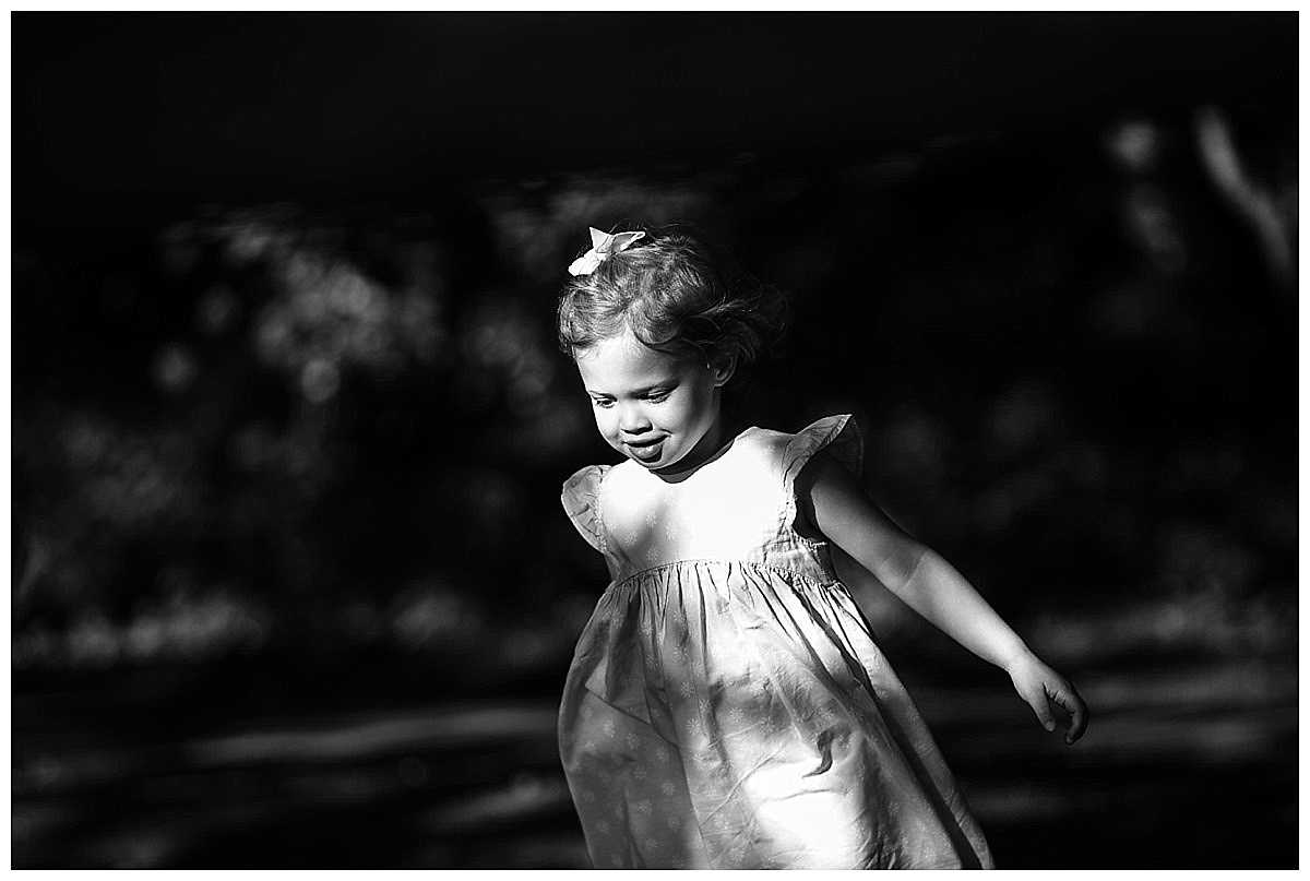 black and white of a little girl running unknown to her about the breeze catching her hair and dress
