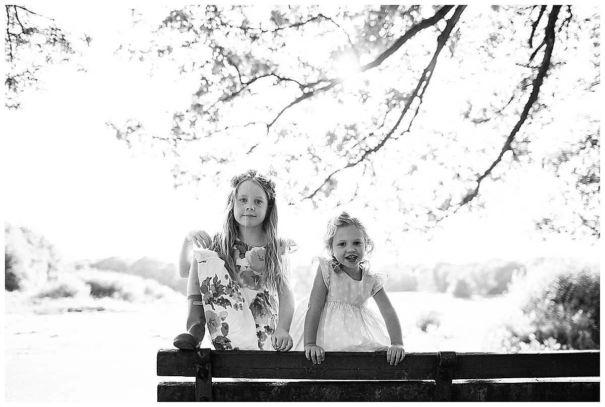 two little girls facing the wrong way leaning on a bench in black and white looking at the camera