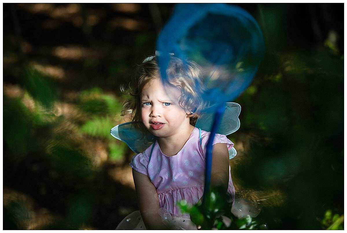 little girl in fairy outfit with a blue net looking at the camera in a beautiful pocket of light - shropshire family photographer