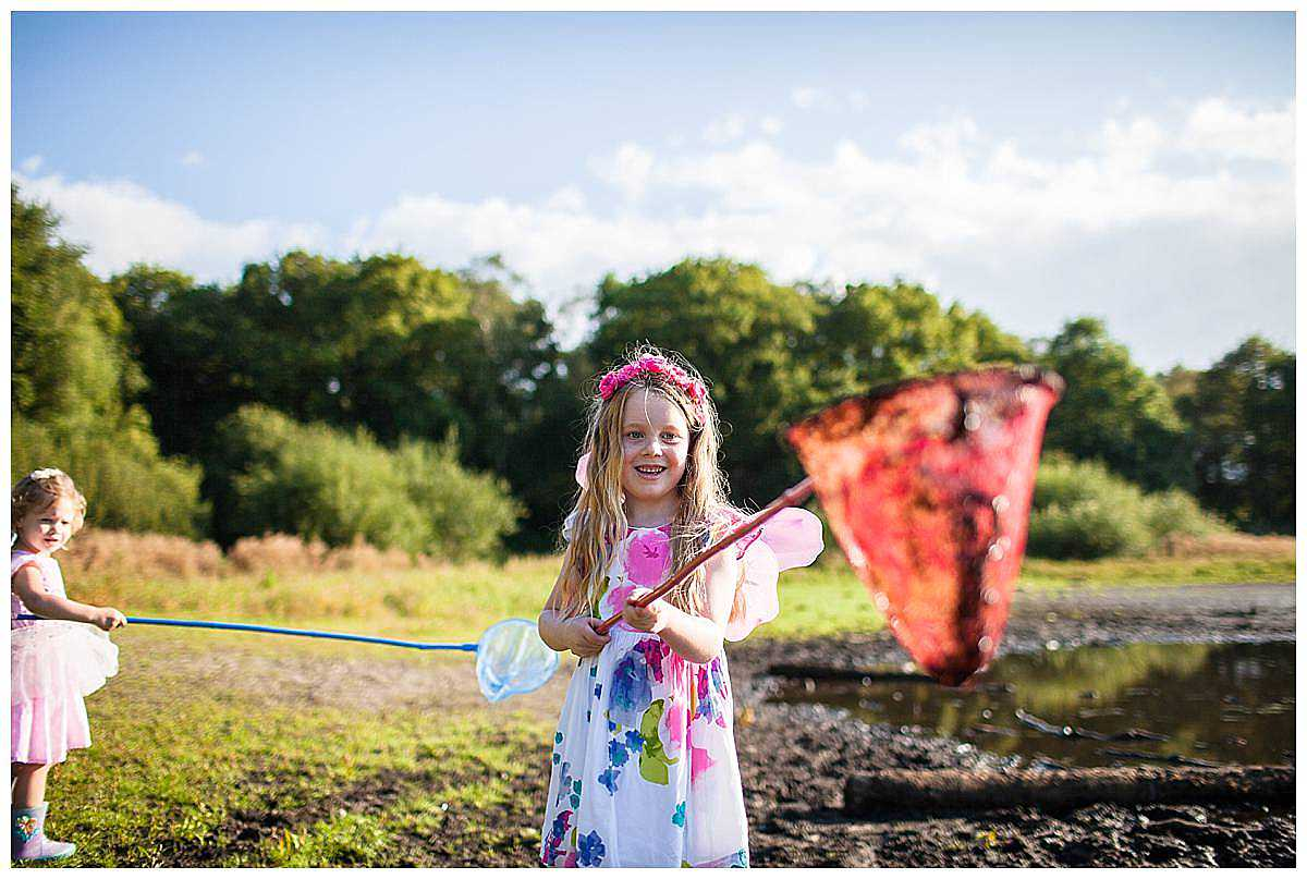little girl in colourful clothes at brown moss, looking amused as she carries mud in her red net - shropshire family photography