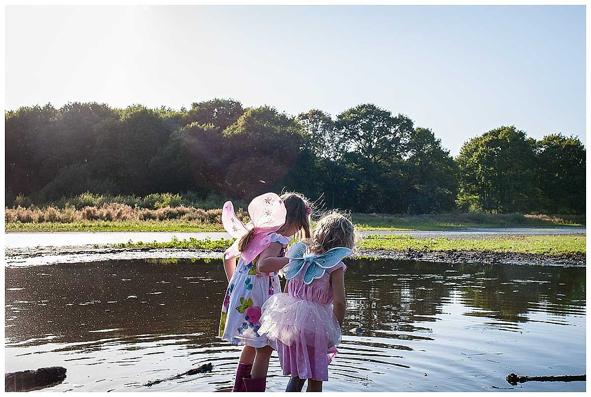 two little girls from behind with little fairy wings on as they play in the water in golden light