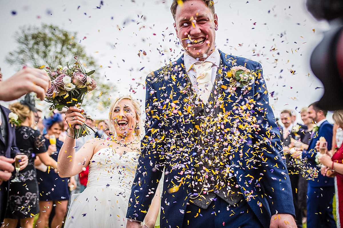 picking your wedding photographer, a shower of confetti thrown at groom during the confetti shot at soulton hall, wem, shropshire, laughing like crazy