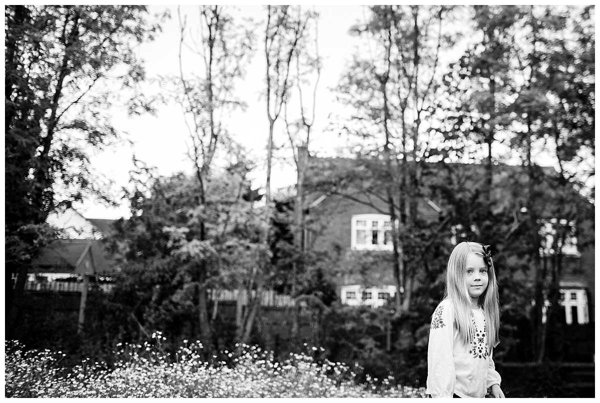black and white photo of little girl looking at the camera while standing in a field looking deep in thought