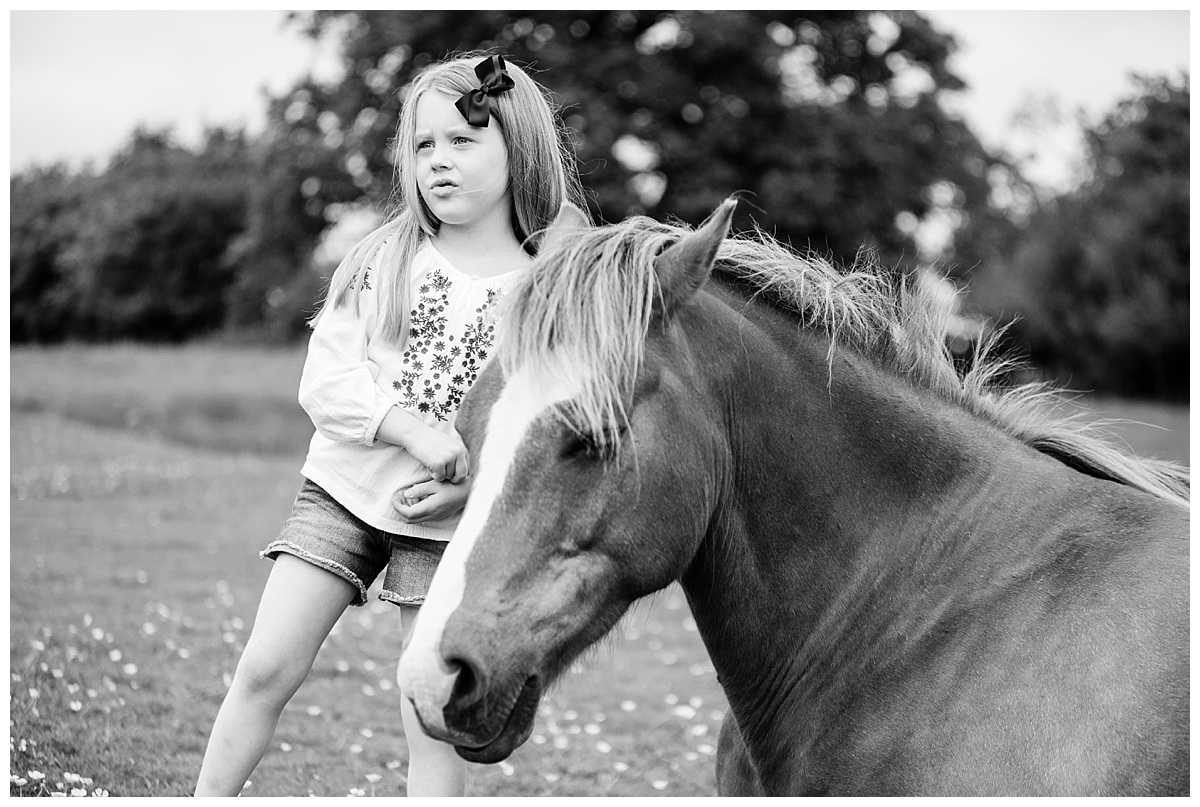 little girl standing next to a horse both looking into the distance- Whitchurch Shropshire Family Photographer