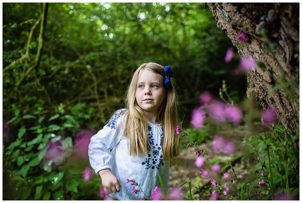 little girl looking over at her mum and dad with beautiful pink flowers in the foreground