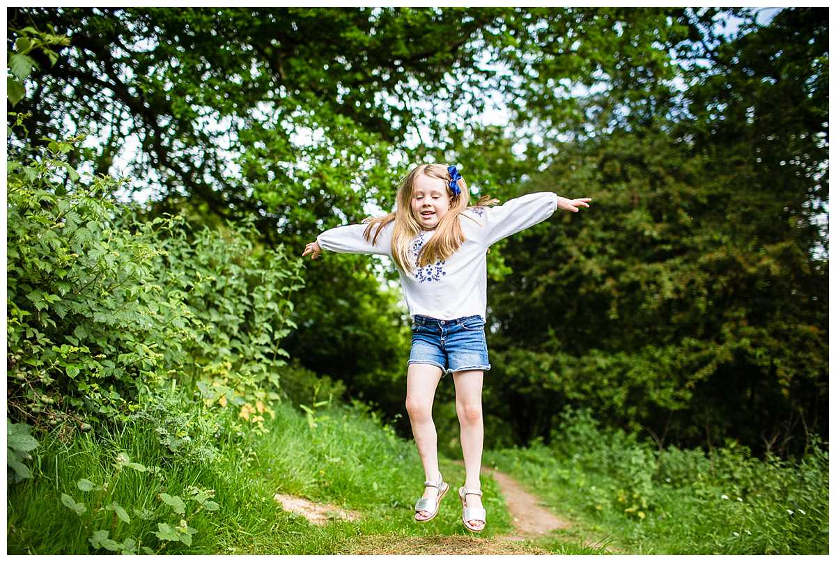 little girl jumping of a mound of soil and hair looking fantastic as it goes in the air