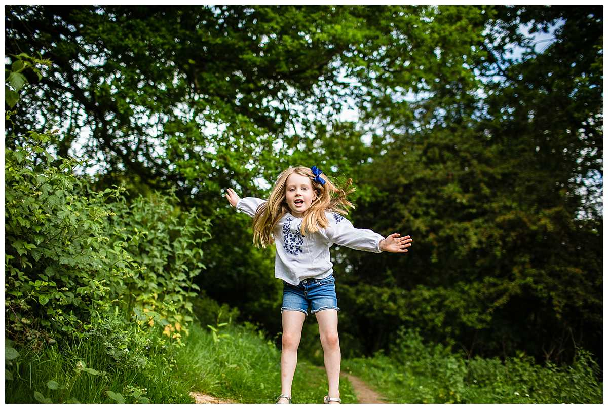 little girl landing as she jumps off a mount of soil, long hair going up in the air