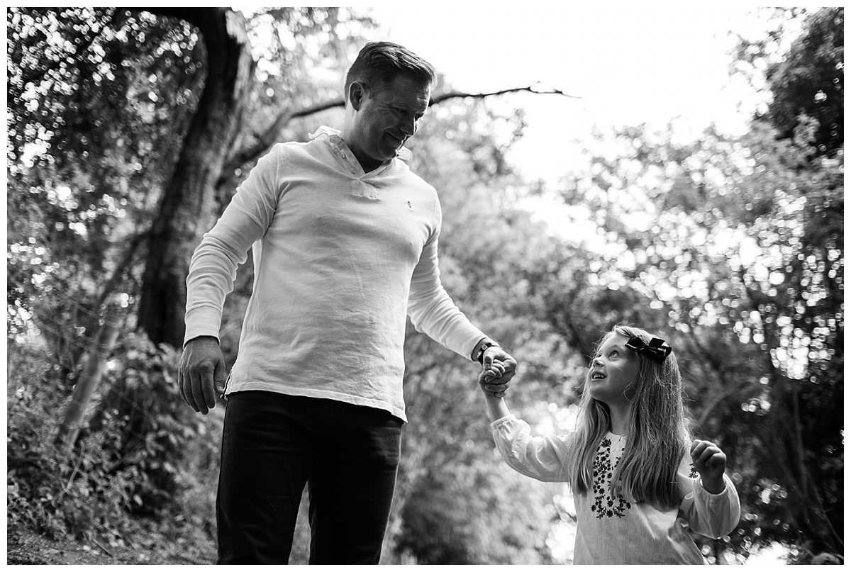 black and white photo of daughter looking up at her dad and gorgeous moment
