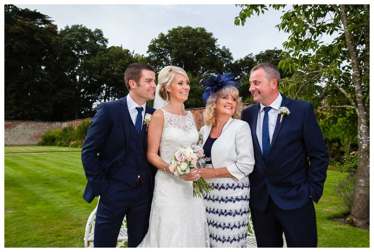 bride and groom with the bride's parents - family photos at combermere abbey wedding, everyone looking at one another very happy