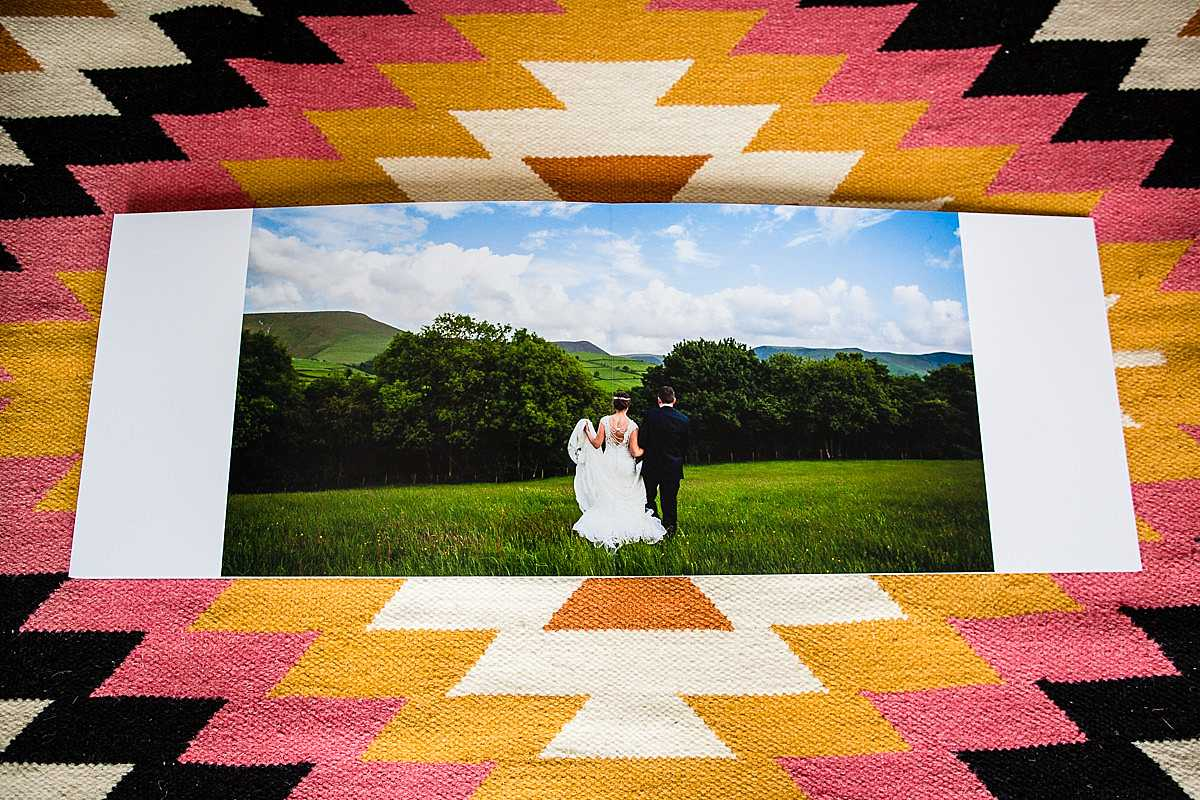 a single photo printed over a double spread with a simple photo of the bride and groom walking straight ahead with a beauitful blue sky and vibrant green view ahead