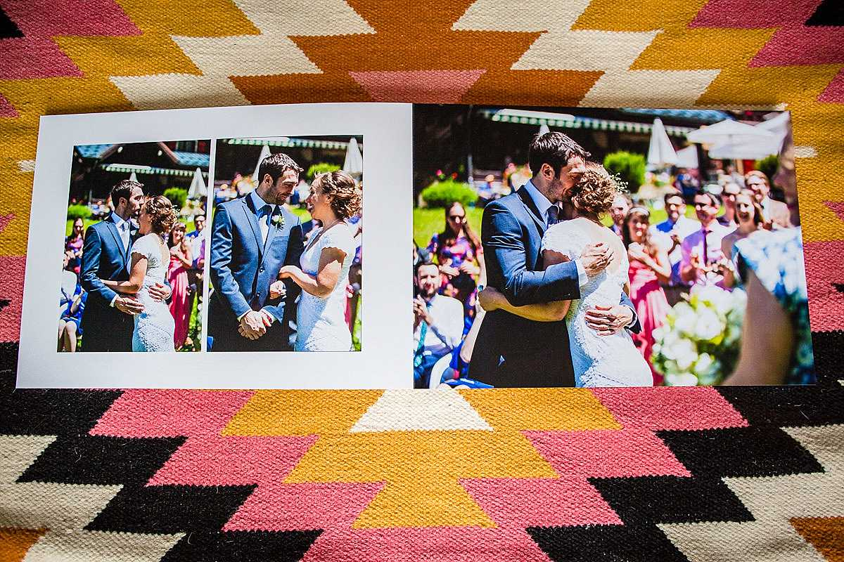 wedding album lying flat open on a spread of bride and groom embracing at the end of their wedding ceremony
