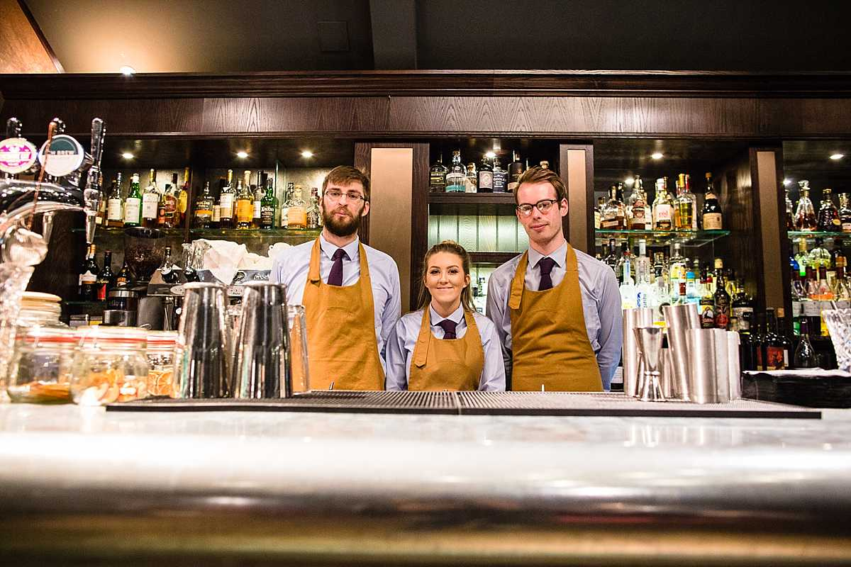 bar staff portrait in sky blue shirts and leather aprons, at 1539 chester race course