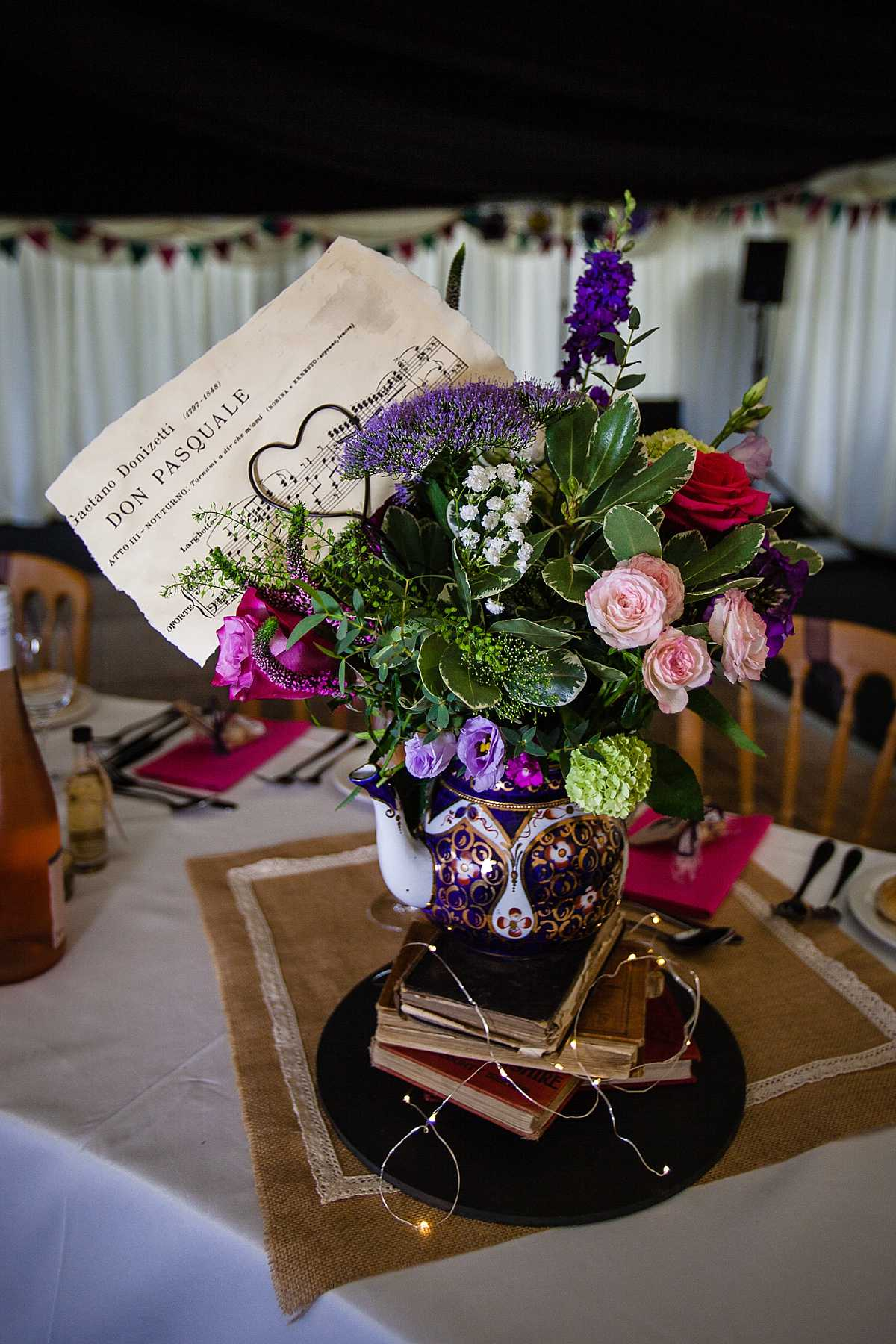 close up of bright colourful flower arrangement in vintage teapot in marquee wedding