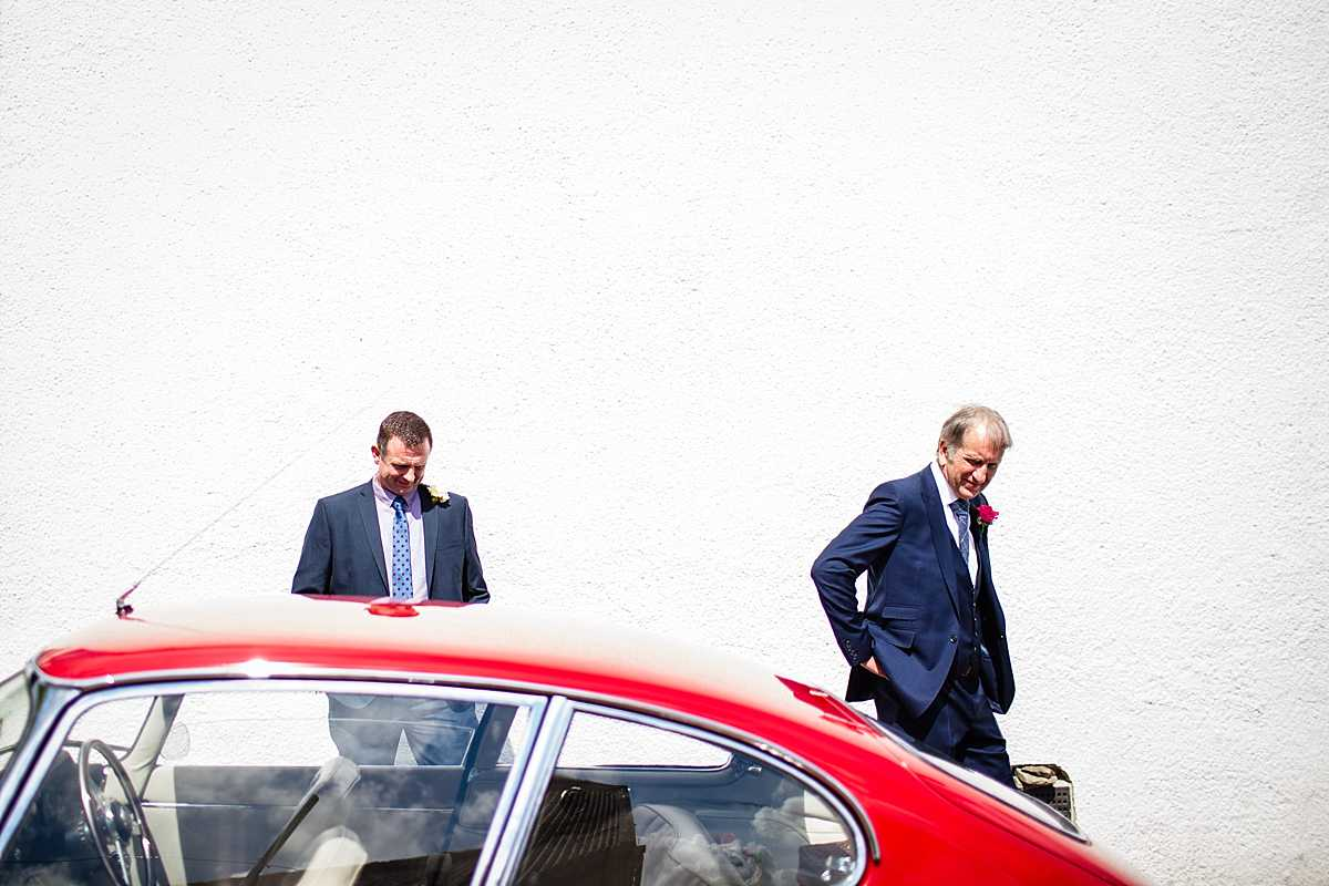 father of the bride checking out the red e-type jaguar parked outside the family home