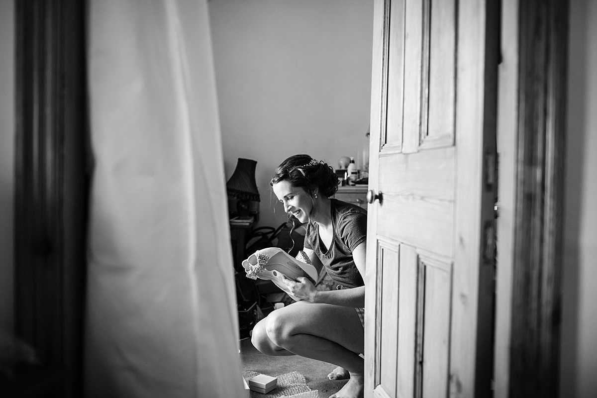 bride bending down next to her wedding dress and looking at her wedding shoes with a big smile on her face