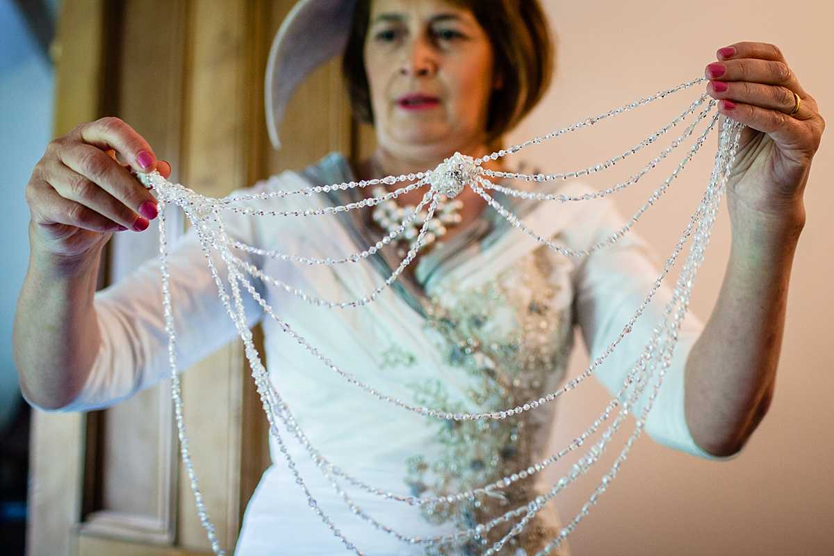mother of the bride picking up beading detail that clips on to a wedding dress - wedding in Machynlleth
