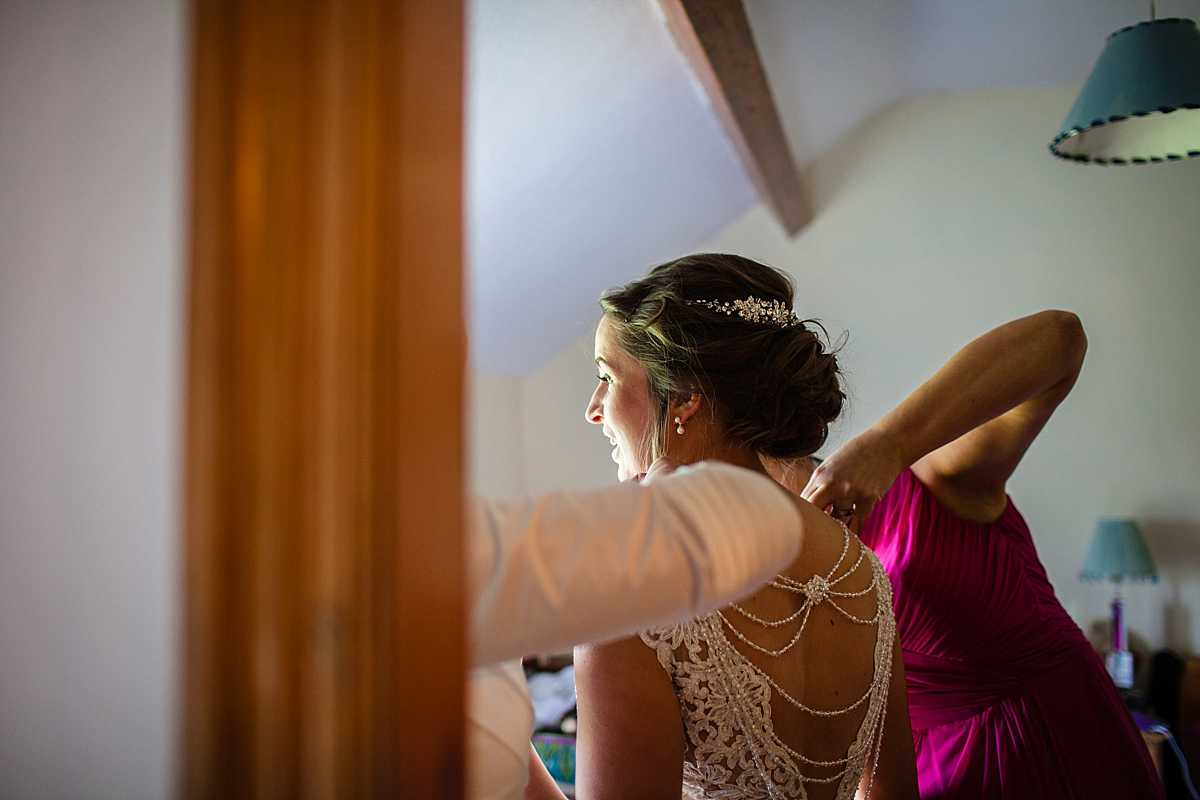 mother of the bride and bridesmaid helping the bride get on her wedding dress