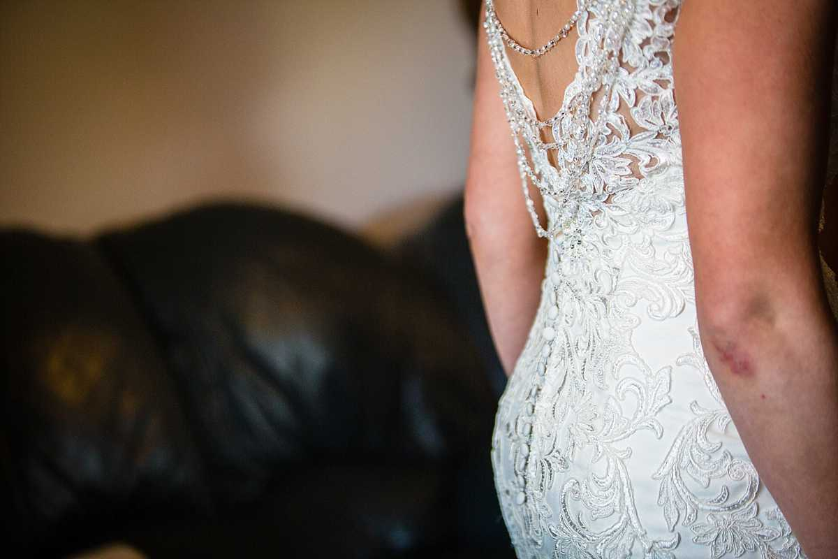 detail shot of the detail in the fabric of the wedding dress and beautiful beading drapping down