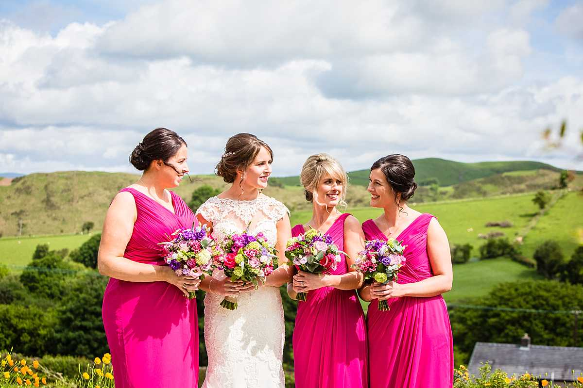 bridesmaids all together looking at one another all ready to go to church in pink bridesmaids dresses - wedding in Machynlleth