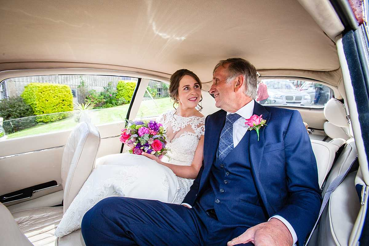 bride and father of the bride sat in red e-type jaguar car lookingat one another looking excited