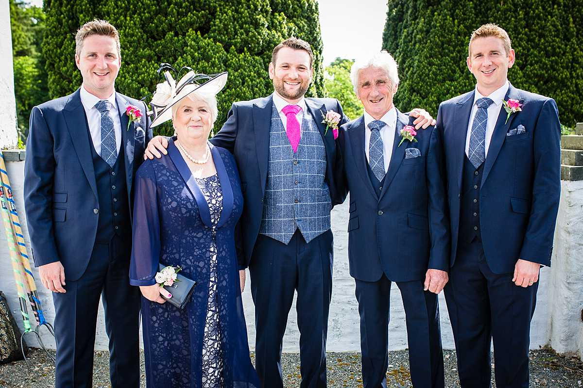 family portrait of a mother and father of the groom with the groom and two brothers who are best men