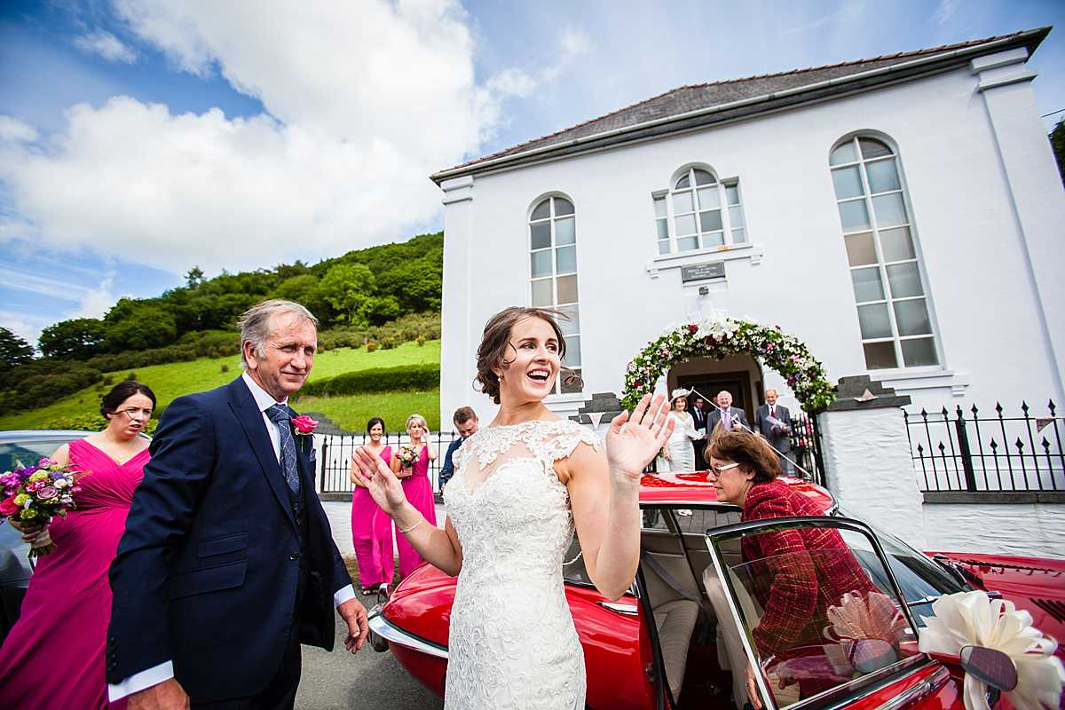 bride getting out of the wedding car and with the expression tah da! as she has got out of the car - wedding in Machynlleth
