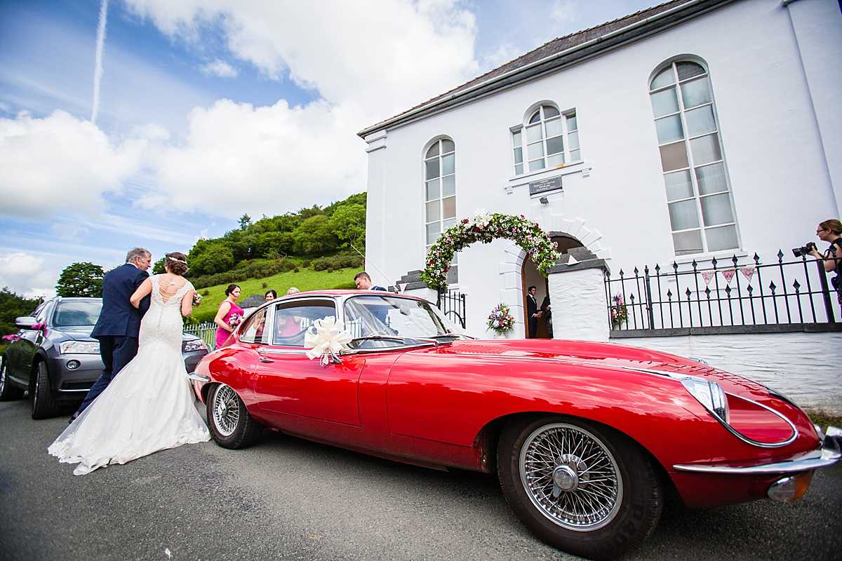 bride linked arms with her dad and she walks towards aberhosan chapel with the beautiful red e-type jaguar and blue sky
