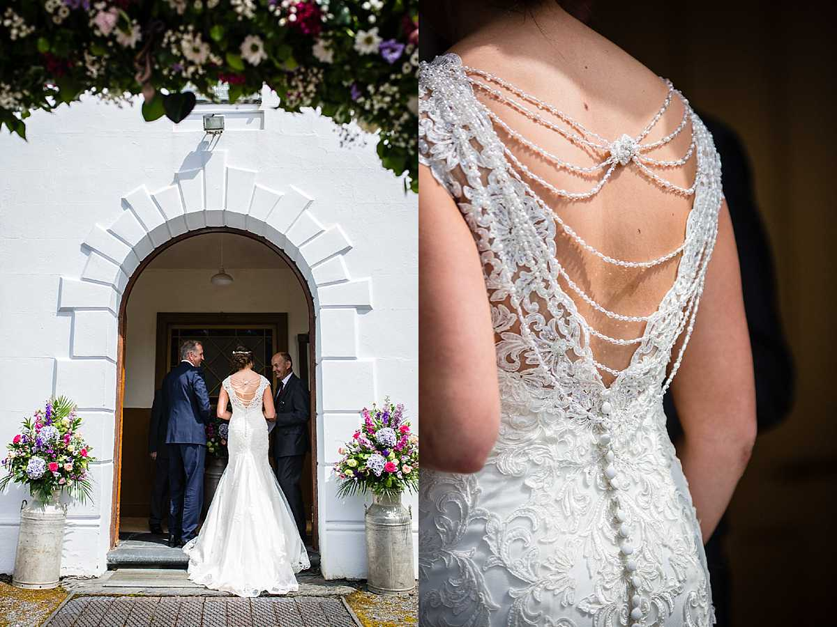 bride standing outside the doorway of white chapel with her dad before she goes in and bead detail of wedding dress