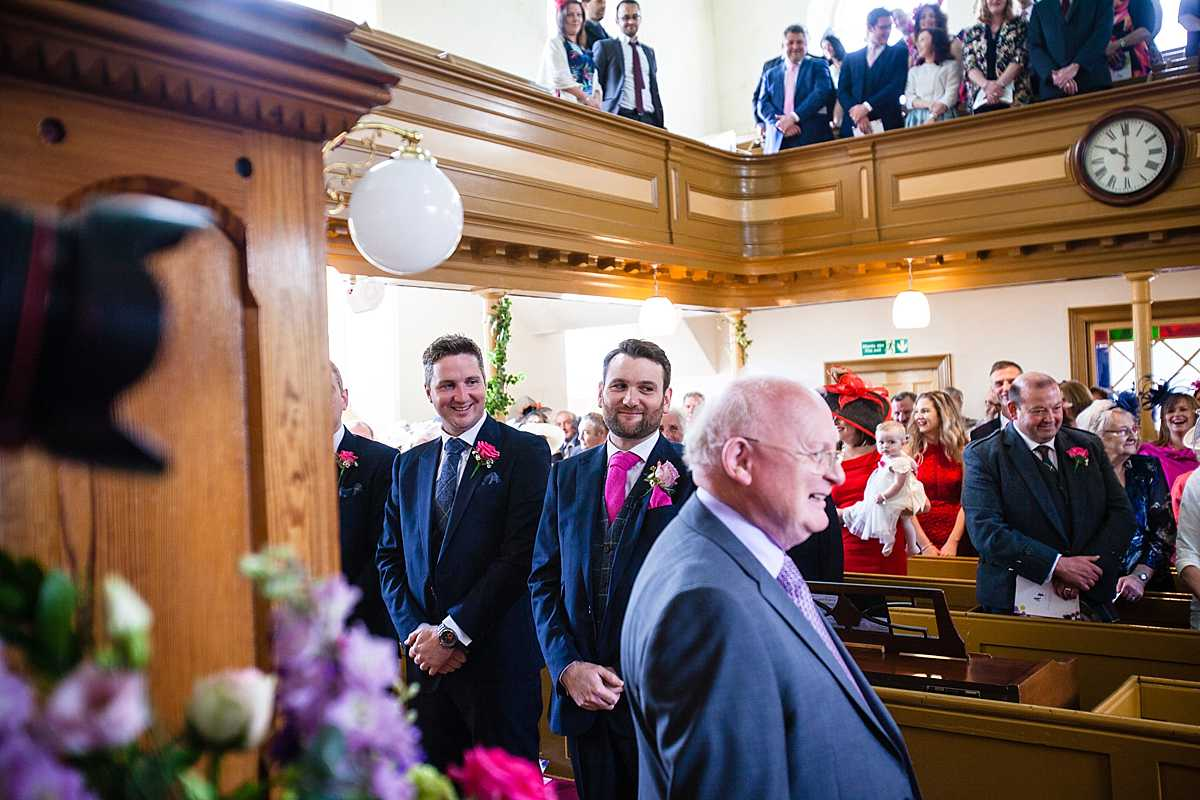 groom looking cheeky at his bride as she gets closer to the alter - wedding in Machynlleth